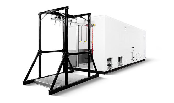 Mobile abattoir in white modular format with a black metal gantry for lifting animals