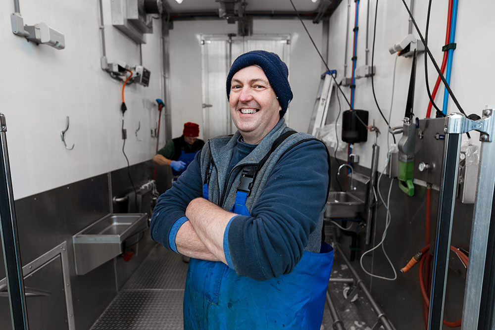 Smiling butcher in blue uniform after completing meat processing in mobile abattoir