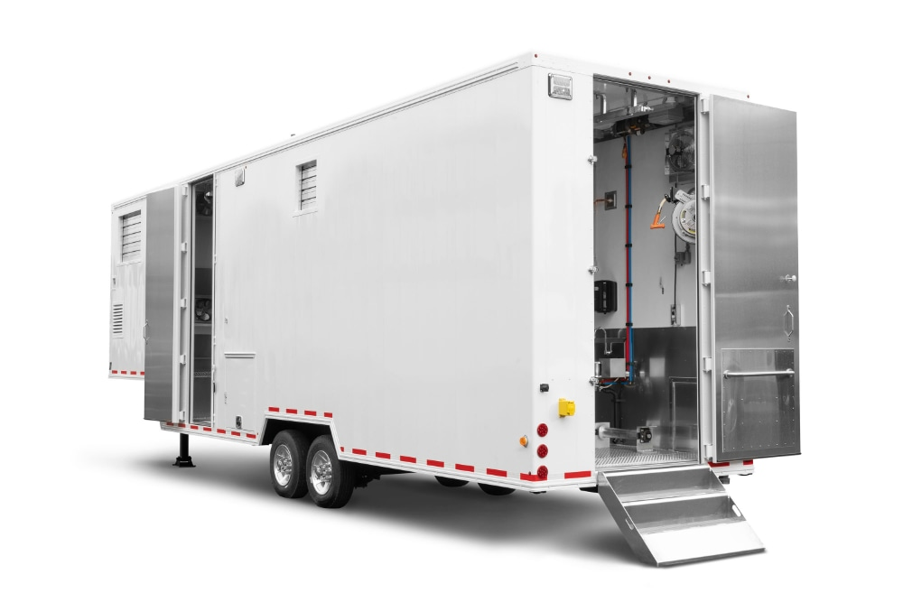 Rear view of mobile harvest unit in white trailer format used for meat processing on farm or ranch